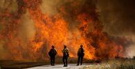 Hasiči v blízkosti hořící trávy v Kalifornii