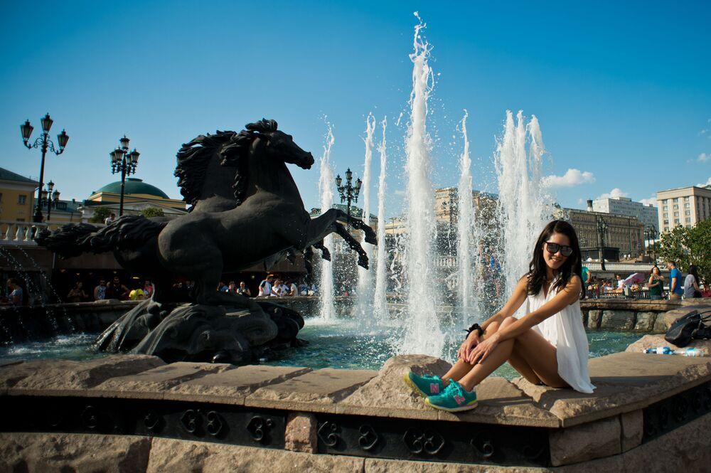 Turisté se fotí vedle fontány na náměstí Manéž, 2016.