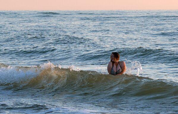 Žena se koupe v Baltském moři poblíž pláže v národním parku Kurská kosa v Kaliningradské oblasti. - Sputnik Česká republika
