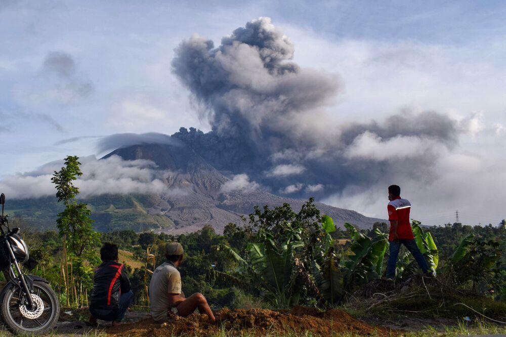 Obyvatelé vesnice pozorují erupci sopky Sinabung na Sumatře, Indonésie.