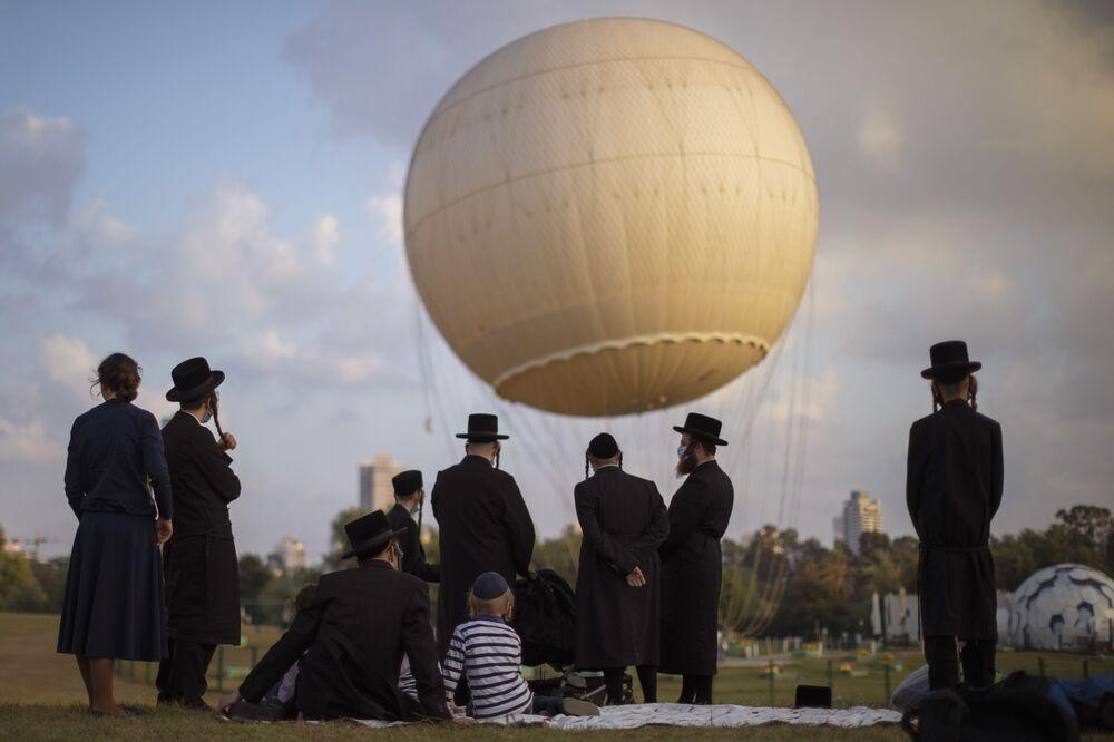 Ultraortodoxní Židé v ochranných maskách v parku v Tel Avivu, Izrael.
