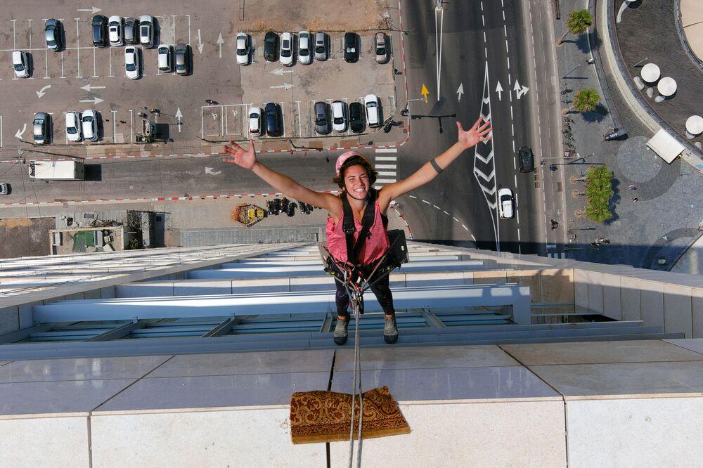 Odborník na mytí oken, Noah Toledo, při práci na výškové budově v Tel Avivu, Izrael.