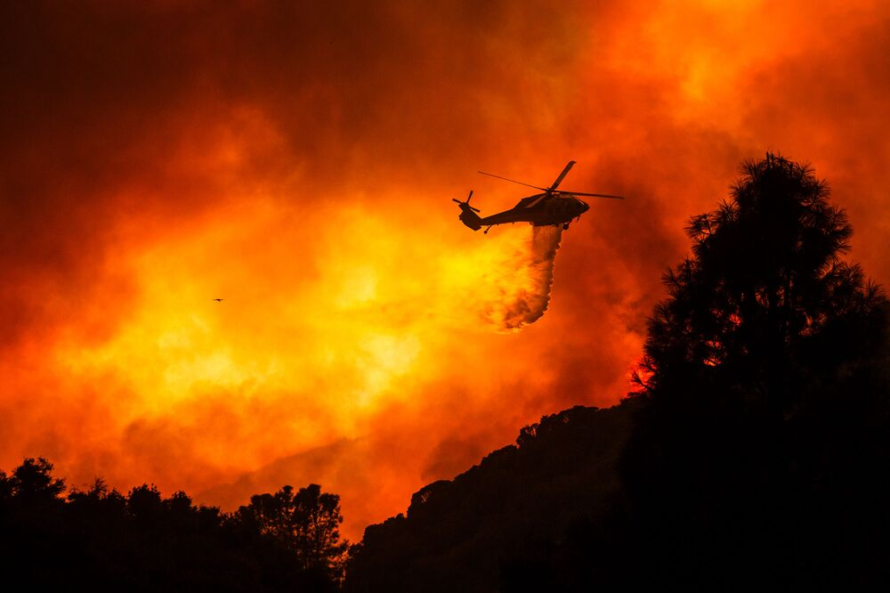Vrtulník nad hořícím lesem nedaleko Santa Clarity, Kalifornie.