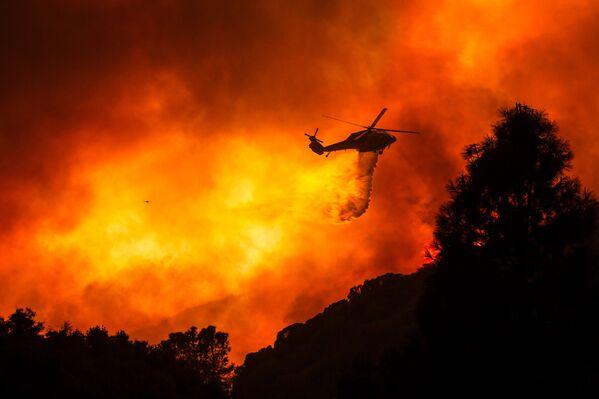 Vrtulník nad hořícím lesem nedaleko Santa Clarity, Kalifornie. - Sputnik Česká republika