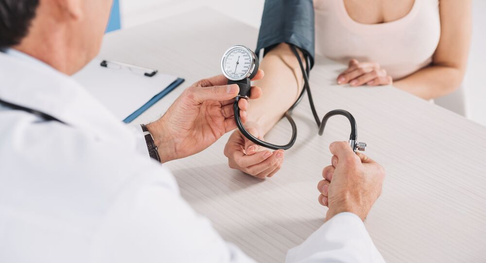 Lékař ženě měří tlak