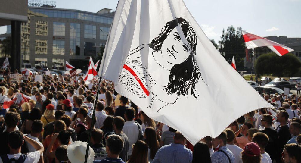 Protestujicí drží vlajku s portrétem Světlany Tichanovské v Minsku