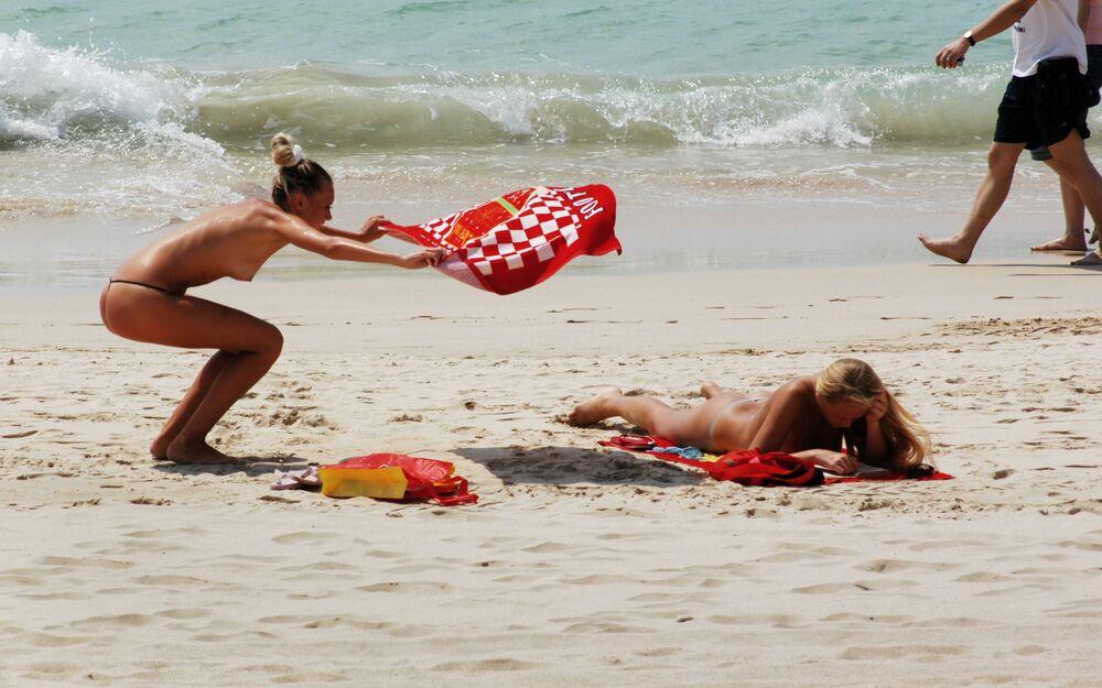Turisté se opalují nahoře bez na čínské pláži
