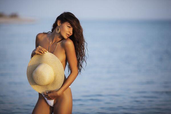 Polonahá dívka s kloboukem na pláži - Sputnik Česká republika