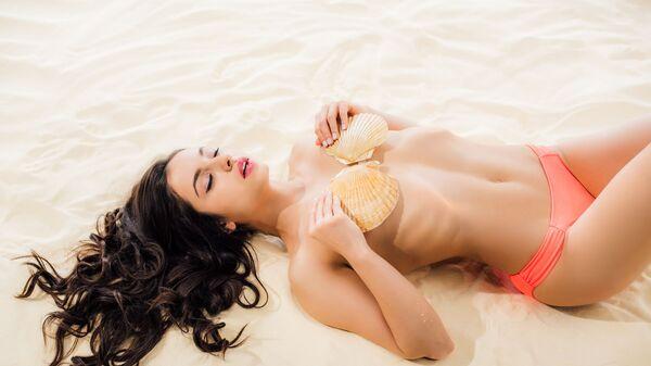 Молодая девушка с ракушками на грудях на пляже - Sputnik Česká republika