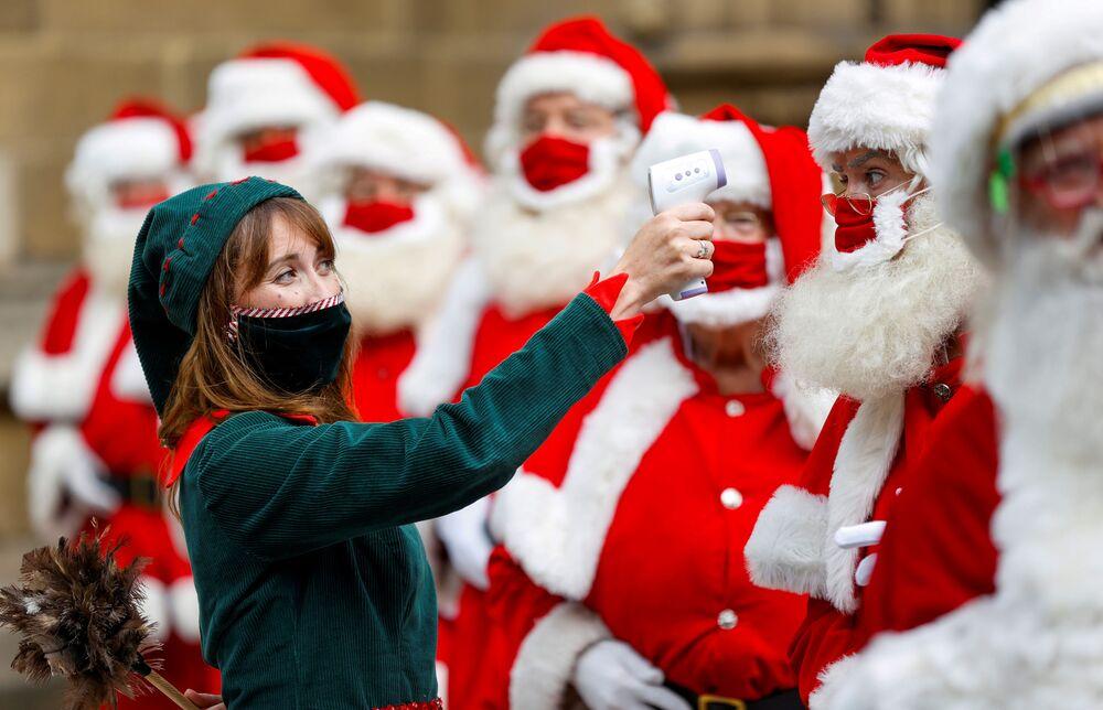 Žena oblečená jako elf s absolventy školy Santa Claus School v Londýně