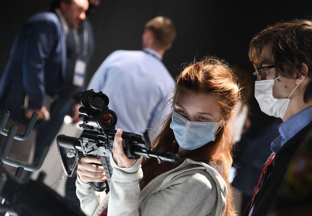Návštěvnice se pozorně dívá na automatickou pušku AK-308 v rámci Mezinárodního vojensko-technického fóra Armáda 2020 ve vojensko-patriotickém parku Patriot