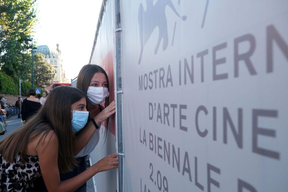 Fanoušci v rouškách šmírují hosty 77. ročníku filmového festivalu v Benátkách.