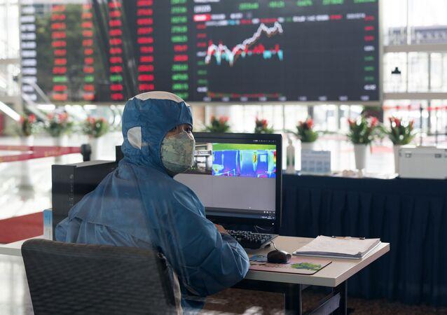 Pracovník v ochranném obleku v hale budovy Šanghajské burzy cenných papírů v čínské Šanghaji