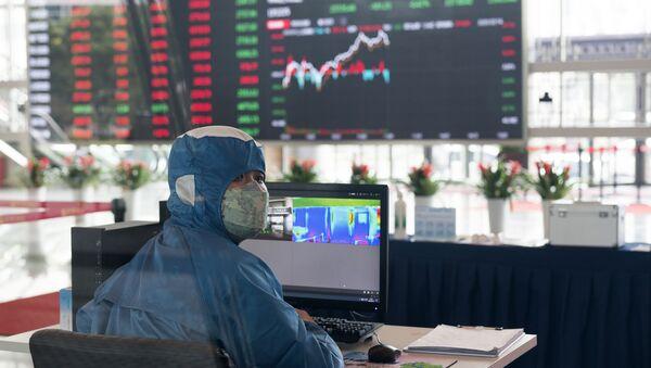 Pracovník v ochranném obleku v hale budovy Šanghajské burzy cenných papírů v čínské Šanghaji - Sputnik Česká republika