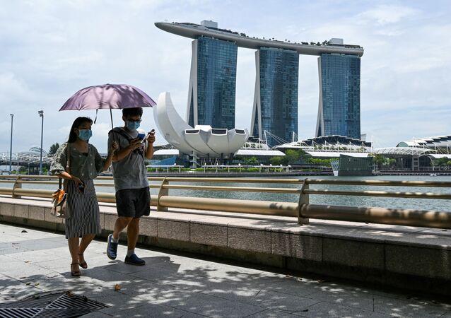 Pár v ochranných rouškách na nábřeží Marina Bay v Singapuru