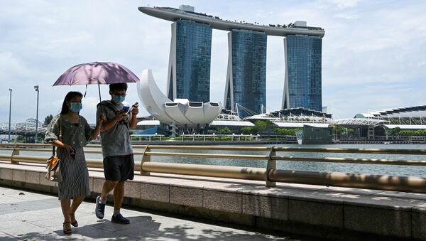 Pár v ochranných rouškách na nábřeží Marina Bay v Singapuru - Sputnik Česká republika