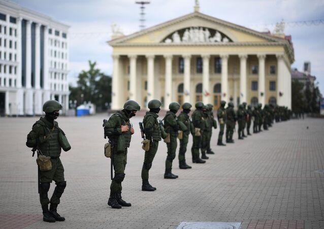 Policisté před neschválenou akcí opozice v Minsku. Ilustrační foto