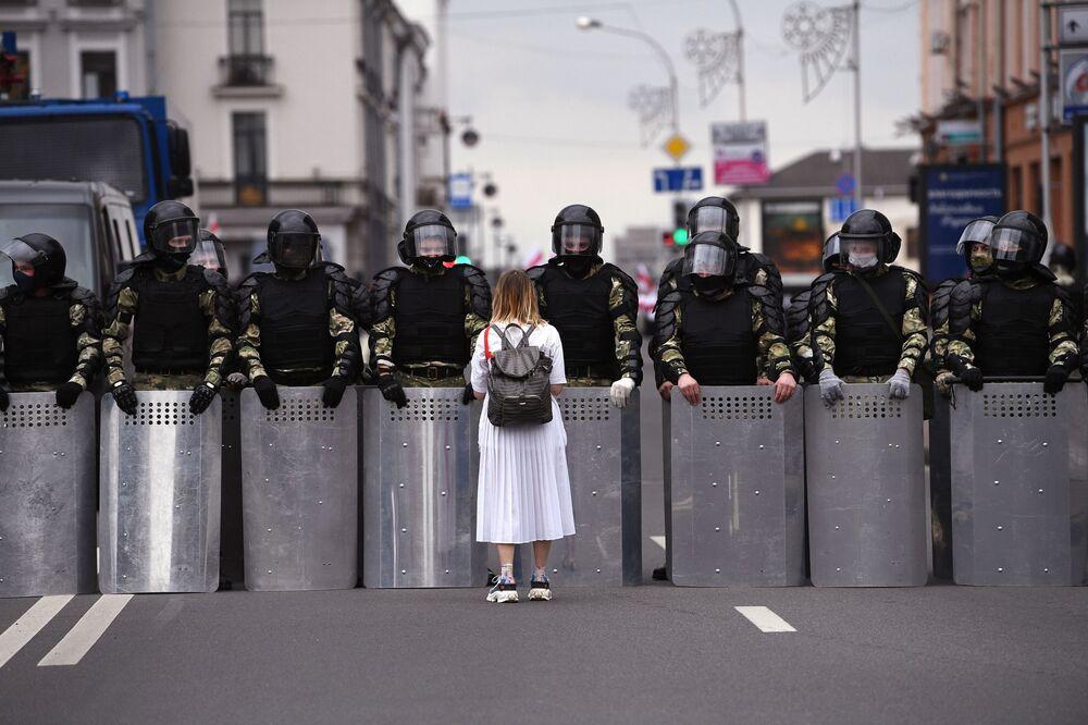Účastník neschválené akce opozice Pochod jednoty a policisté na ulici v Minsku