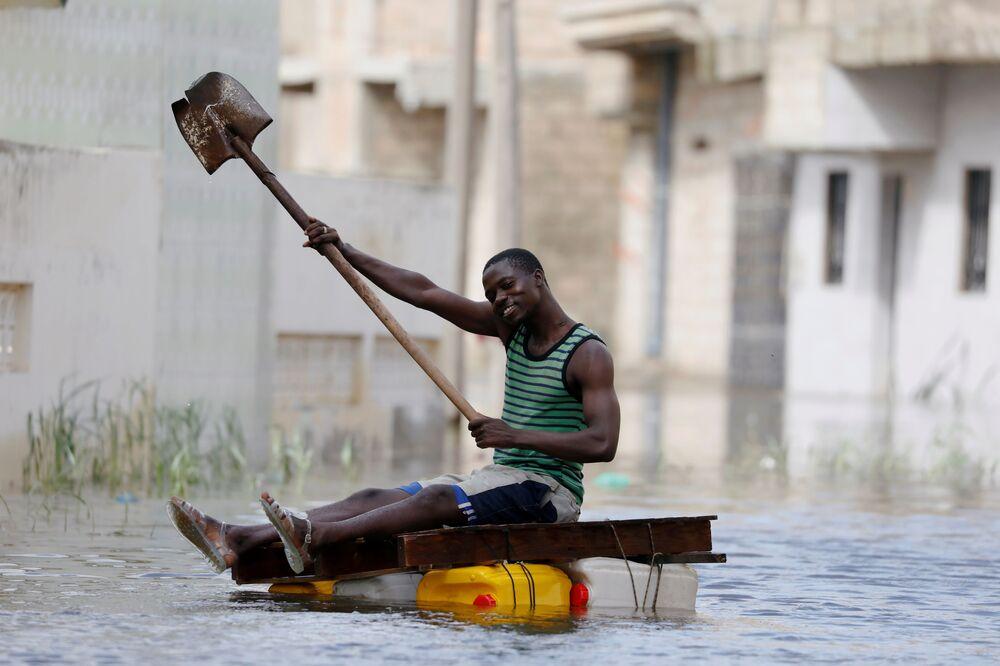 Obyvatel na provizorním voru s lopatou proplouvá zaplavenými ulicemi po silných deštích v Keur Massar, Senegal