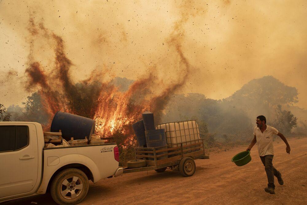 Dobrovolník se snaží uhasit požár na silnici v Brazílii