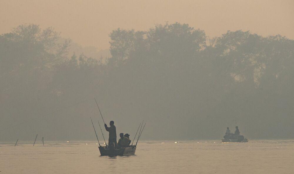Muži rybaří na řece Cuiaba zahalené kouřem od lesních požárů