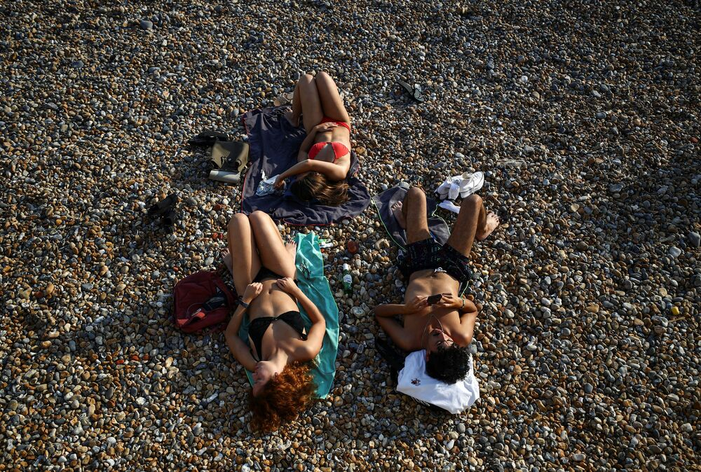 Lidé odpočívají na pláži Brighton v Anglii