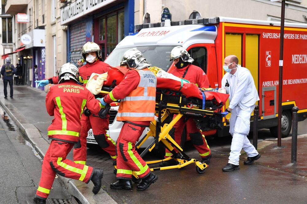 Francouzští hasiči odváží zraněného člověka po incidentu, k němuž došlo poblíž budovy bývalé redakce satirického časopisu Charlie Hebdo