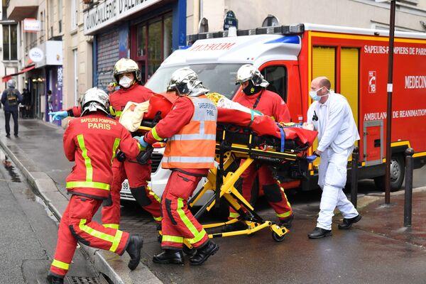 Francouzští hasiči odváží zraněného člověka po incidentu, k němuž došlo poblíž budovy bývalé redakce satirického časopisu Charlie Hebdo - Sputnik Česká republika