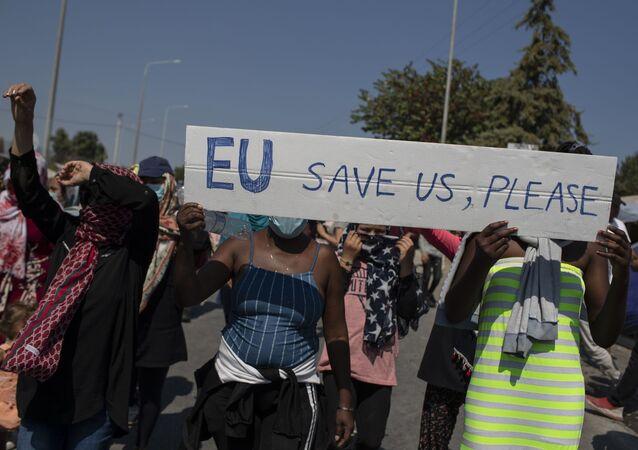 """Migranti drží transparent """"EU, zachraň nás, prosíme"""" během protestů u města Mytiléna na ostrově Lesbos v Řecku"""