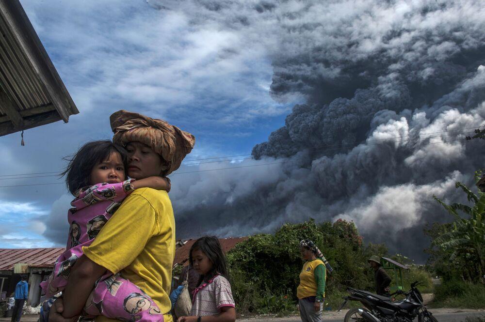 Místní obyvatelé u stratovulkánu Sinabung v Indonésii