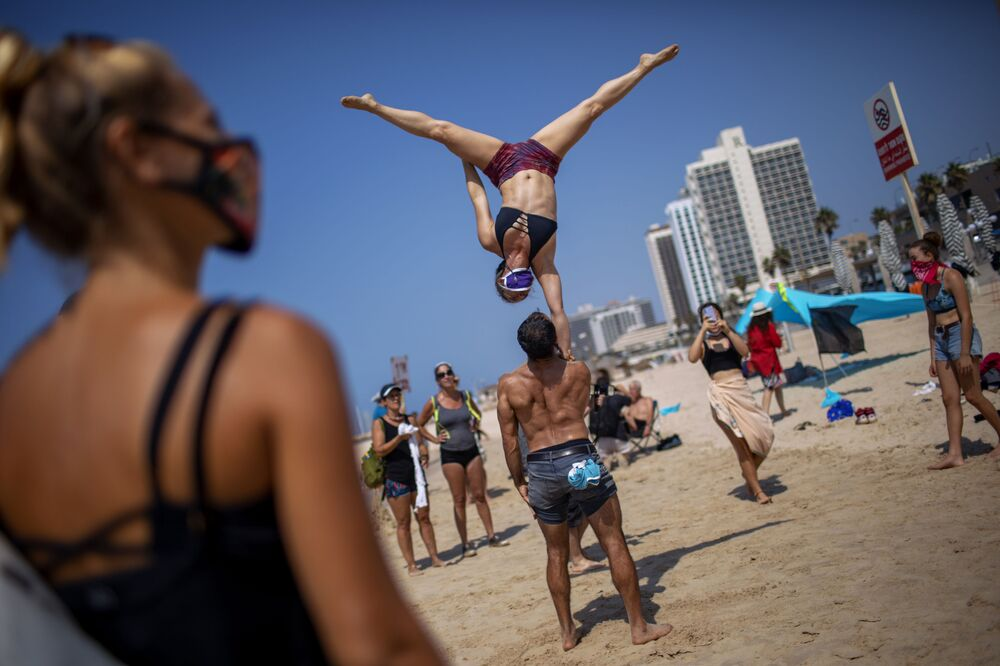 Vystoupení akrobatů během protestní akce proti rozhodnutí vlády uzavřít pláže kvůli pandemii koronaviru. Tel-Aviv, Izrael