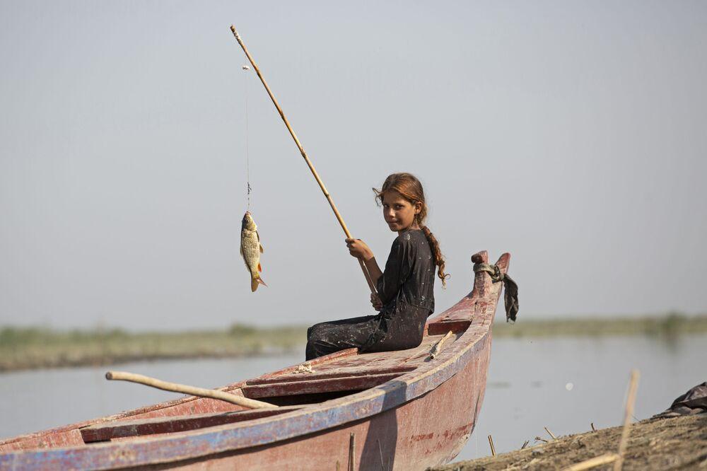 Dívka rybaří poblíž Basry, Irák