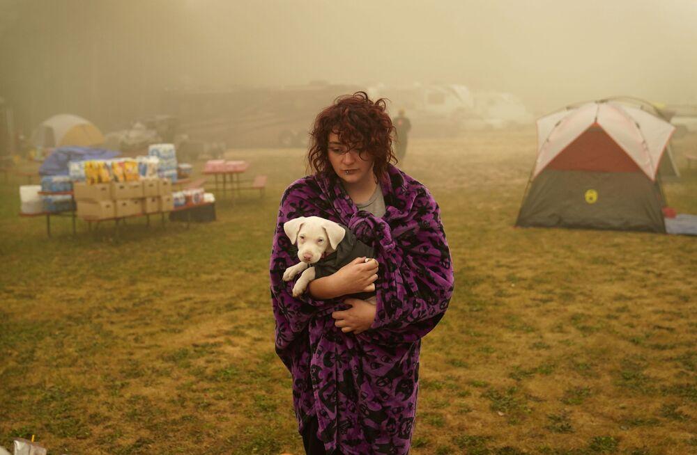 Žena drží svého psa zabaleného do deky v evakuačním středisku v Oak Grove v Oregonu.