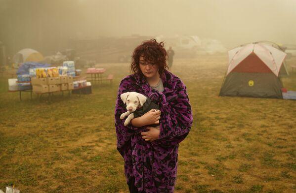 Žena drží svého psa zabaleného do deky v evakuačním středisku v Oak Grove v Oregonu. - Sputnik Česká republika