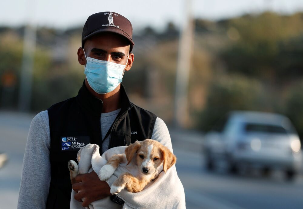 Uprchlík se spolu se psem stěhuje do nového dočasného tábora pro migranty a uprchlíky na řeckém Lesbu.