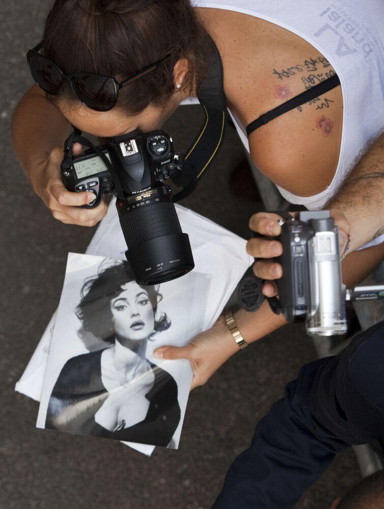 Fanoušci Moniky Bellucci při čekání na zahájení tiskové konference s její účastí, 2. září 2011.