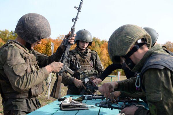 Čištění zbraní před střelbou z ručních palných zbraní během kvalifikačních zkoušek na právo nošení karmínového baretu  - Sputnik Česká republika