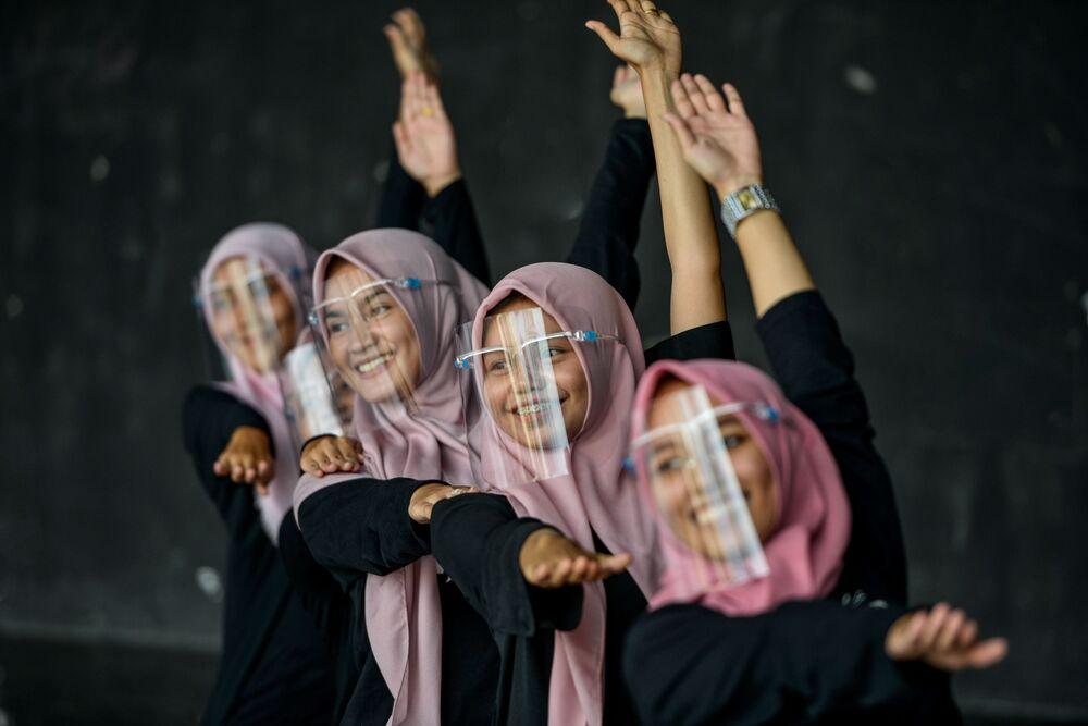 Dívky v ochranných maskách na obličeji při tréninku v uměleckém a kulturním centru v Bunda Acehu, Indonésie