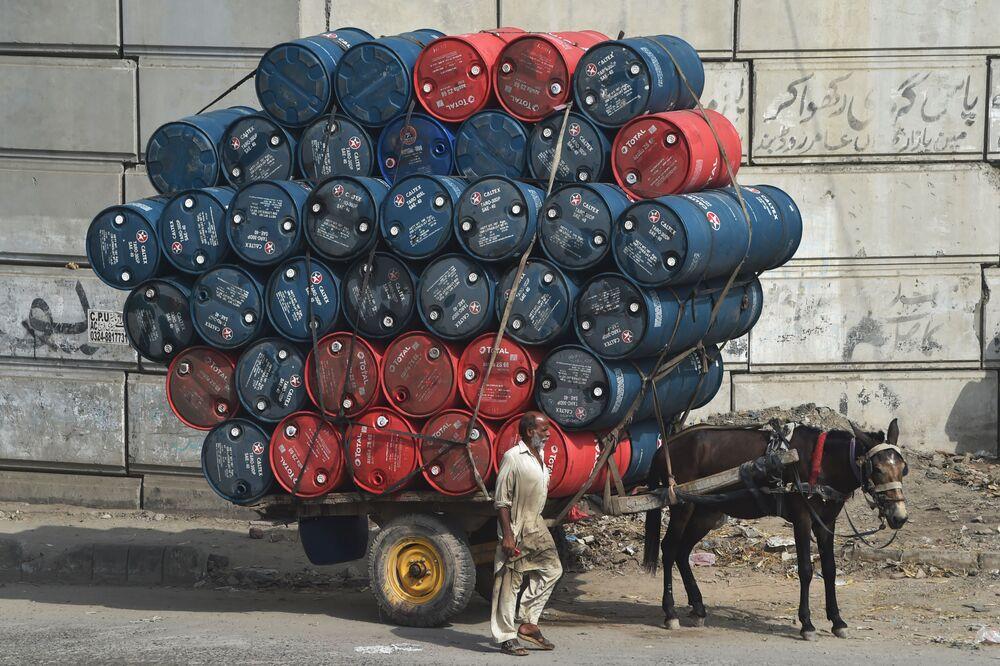 Muž doprovází osla táhnoucího povoz naložený sudy s ropou v Láhauru, Pákistán