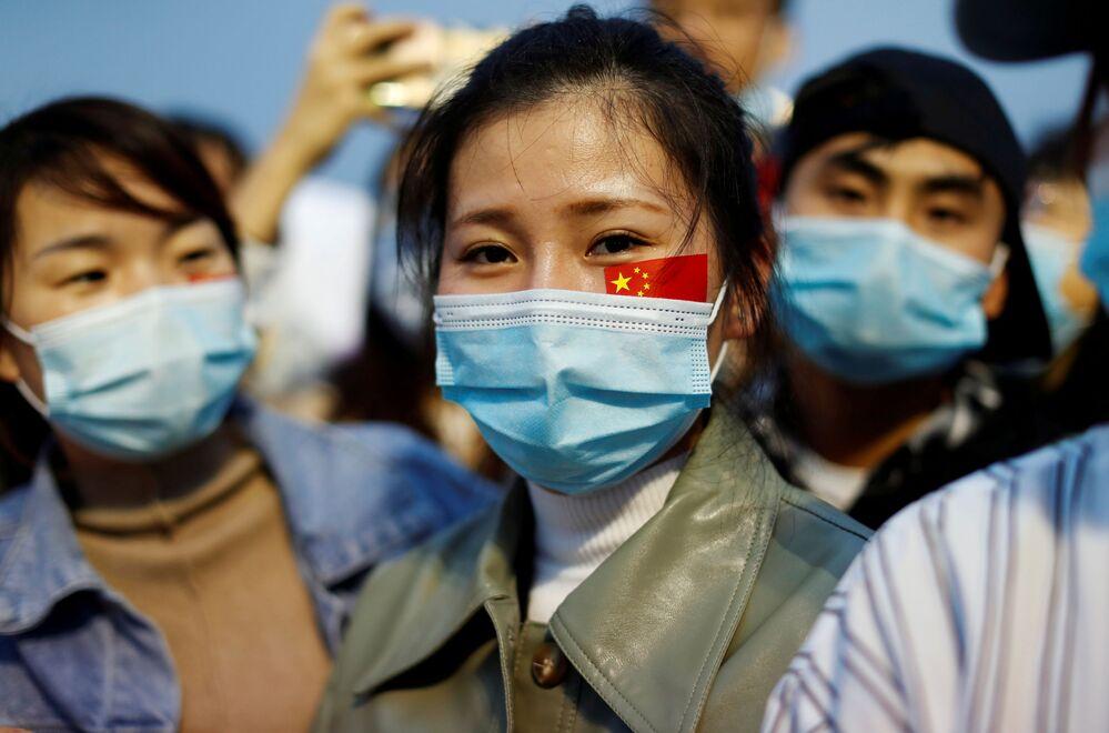 Lidé v maskách na slavnostním ceremoniálu vztyčení vlajky na náměstí Tchien-an-men na počest 71. výročí založení ČLR