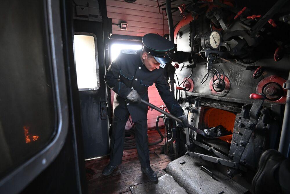 Strojvůdce nakládá uhlí do pece