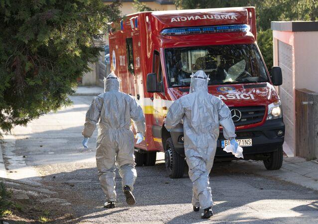 Sanitky a zdravotníci v ochranných oblecích u domu v Bratislavě