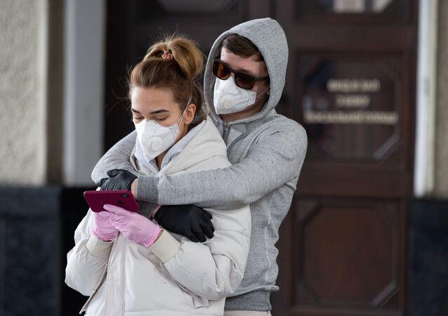Mladí lidé hledí na telefon v době pandemie koronaviru