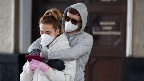 Mladí lidé hledí na telefon v době pandemie koronaviru - Sputnik Česká republika