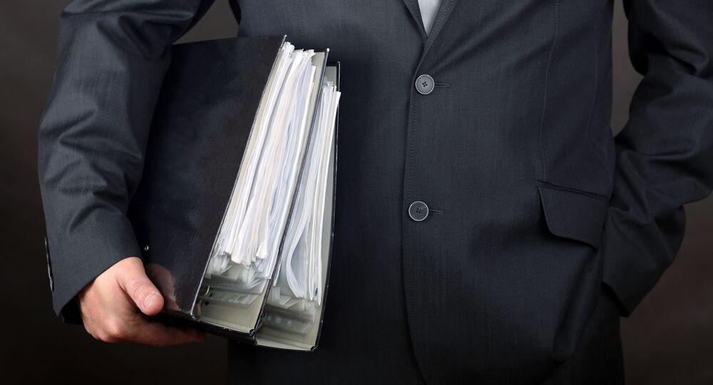 Muž se složkami s doklady v ruce