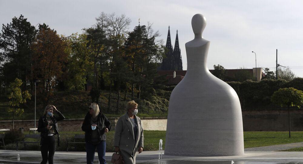 Kolemjdoucí v lékařských rouškach před pomníkem Marie Terezie v Praze