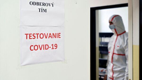 Muž v individuálních ochranných prostředcích na testovací stanici na covid-19 na základní škole ve městě Dolný Kubín na Slovensku - Sputnik Česká republika