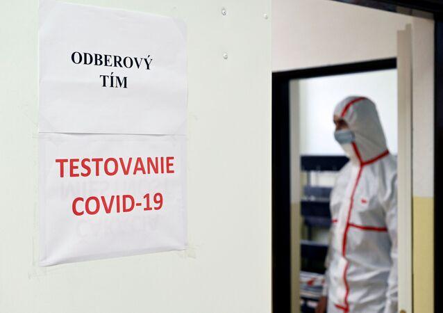 Muž v individuálních ochranných prostředcích na testovací stanici na covid-19 na základní škole ve městě Dolný Kubín na Slovensku