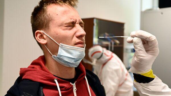 Zdravotnický pracovník odebere vzorek výtěru od osoby na testovacím místě na covid-19 v Oravském Podzamku na Slovensku - Sputnik Česká republika