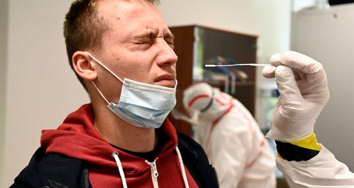 Zdravotnický pracovník odebere vzorek výtěru od osoby na testovacím místě na covid-19 v Oravském Podzamku na Slovensku